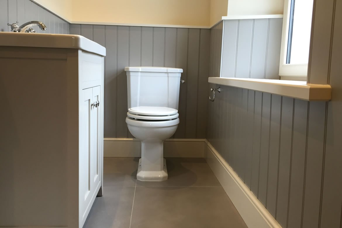small bathroom installation with sink unit and toilet at the end